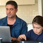 Man working from home surrounded by her two children and wife 8 ways to work from home effectively during lockdown blog